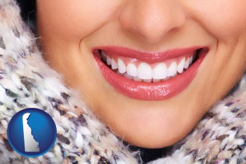 beautiful white teeth forming a beautiful smile - with Delaware icon